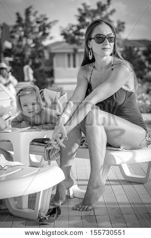 Black And White Photo Of Young Mather Resting Near The Pool
