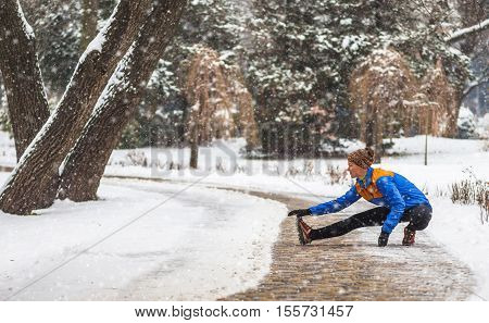 Young sport woman doing exercises during winter training outside in cold snow weather in park