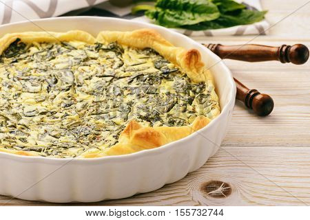 Tart with spinach and eggs on white background.