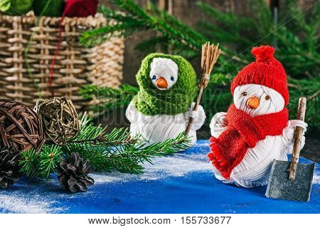 Handmade yarn snowmen holding shovel and broom on the background of christmas decorations
