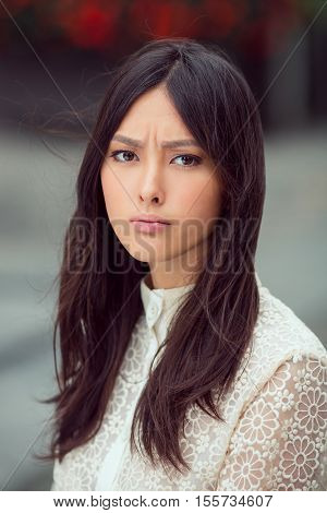 Sad woman - portrait of upset fanny beautiful mixed race Asian Caucasian young girl outdoor against city blurred bokeh background
