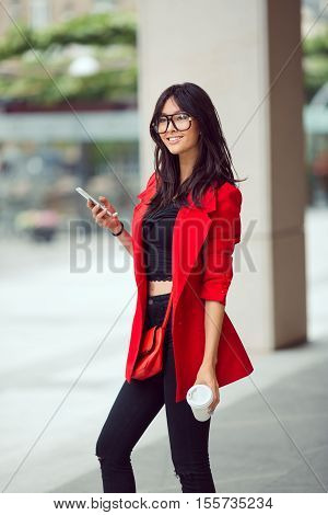 Young pretty businesswoman texting outdoors. Beautiful young stylish asian woman in red casual suite and glasses with phone and cup of coffee smiling and looking at camera against street background