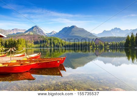 Dreamy red boats stand at the pier on a quiet lake with a beautiful view of the mountains.Strbske Pleso lake Slovakia Tatra mountains