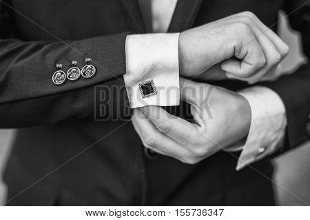 Elegant young fashion man looking at his cufflinks while fixing them, black and white photo