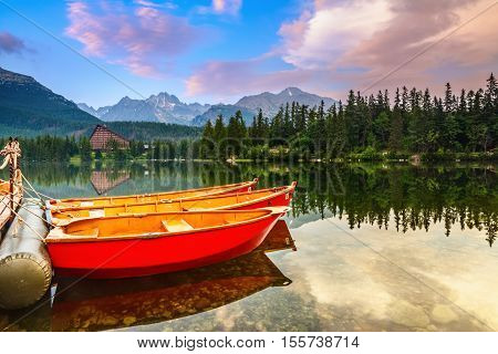 Beautiful high mountains around the incredibly magic lake with red boats and canoe on a spring day.Strbske Pleso lake Slovakia Tatra mountains.