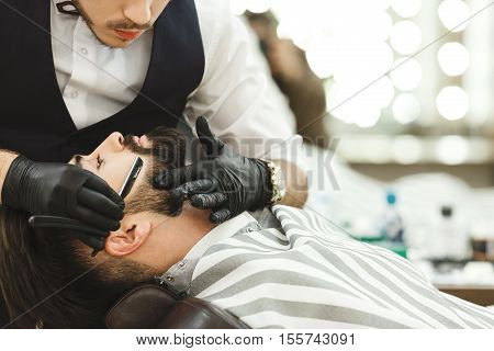 Man's hands wearing black gloves and watch making a beard form with razor for man with dark hair and beard at barber shop, portrait, copy space.