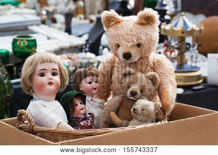 bunch of old dolls and old teddies at a flea market
