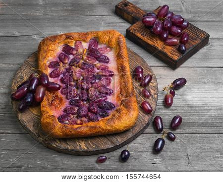 Homemade Galette or crusty pie with purple grapes. Grapes for pie on board. Grapes on the table. Gray wooden background.