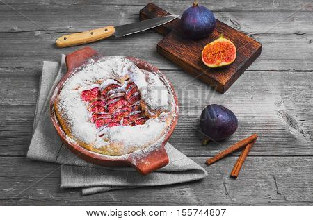 Tart pie with figs and powdered sugar. Fresh fruits purple figs for pie on board. Cut figs cinnamon. Gray wooden background table knife.