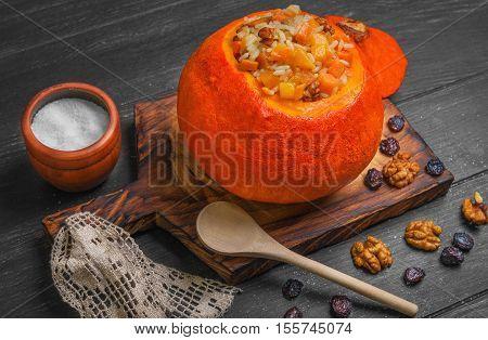 Halloween Pumpkin risotto with raisins. Rice porridge with sweet pumpkin raisins nuts. Baked pumpkin Halloween for rice. Sugar dark wooden background.