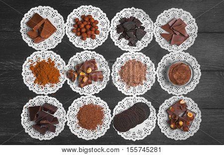 Chocolate assortment ingredients texture. Cocoa powder cocoa mass chocolate paste chocolate candy chocolate cookies broken chocolate almonds hazelnuts Dark black wooden background Top view