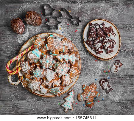 Christmas sweets baking gingerbread cookies on the plate. Forms for Christmas gingerbread cookies chocolate christmas figurines bumps. Christmas cookies gingerbread on white light table. Top view