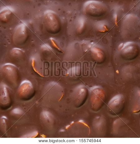 Texture of milk chocolate with nuts. Brown milk chocolate almonds nuts background. Top view.