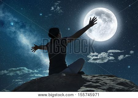 woman sitting and raising arms in the moonlight