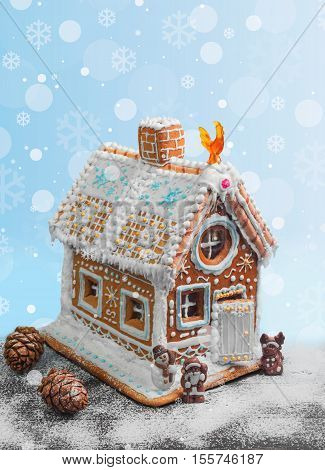 New Year Christmas gingerbread house decorated with icing sugar snow. Christmas figure Santa Claus reindeer snowman next to gingerbread house. Christmas rooster symbol of new year gingerbread house. Isolated on white