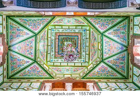 KAIROUAN TUNISIA - AUGUST 30 2015: The ceiling of hall in Mansion of Governor decorated with painted floral patterns and beautiful chandelier on August 30 in Kairouan.