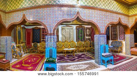 KAIROUAN TUNISIA - AUGUST 30 2015: Panorama of Great Meating Room in Mansion of Governor with fine patterns on glazed tile old carpets and carved wooden furniture on August 30 in Kairouan.