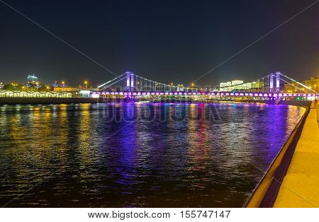 The Krumsky (Crimean) suspension Bridge over the Moskva River in colorful evening lights Moscow Russia.