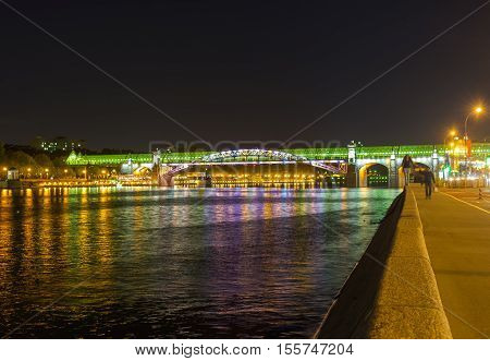 The night walk along the Frunzenskaya embankment to the Pushkinsky (also named Andreevsky) Pedestrian Bridge Moscow Russia.