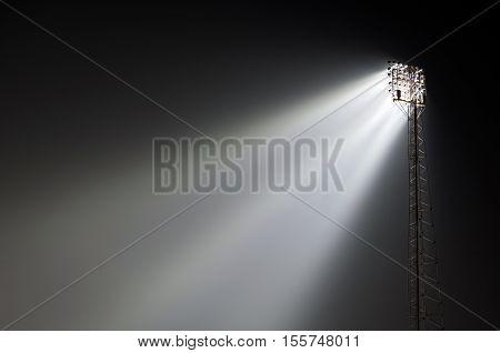 Sports ground stanchion flood lights lit up at night