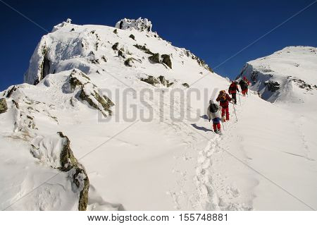 People Hiking In Beautiful Winter Mountains