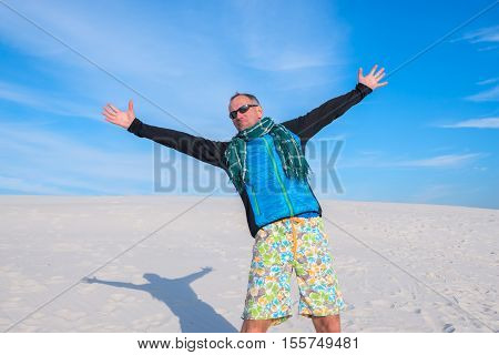 Smiling man with arms outstretched by the desert on the background of the bright blue sky. Wide angle.