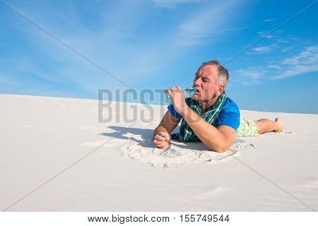 Man hiker suffering from thirst in the desert eagerly drinking water from a small plastic bottle.