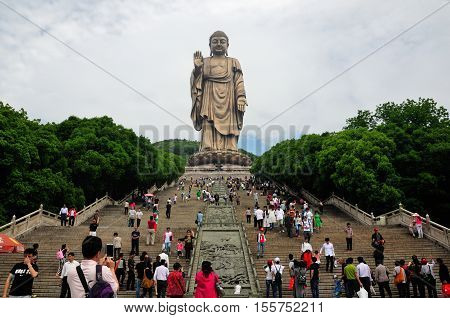 May 17 2015. Wuxi China. Chinese tourists taking pictures and climbing up the stone steps leading up to the Lingshan Buddha statue in Wuxi China in Jiangsu province.