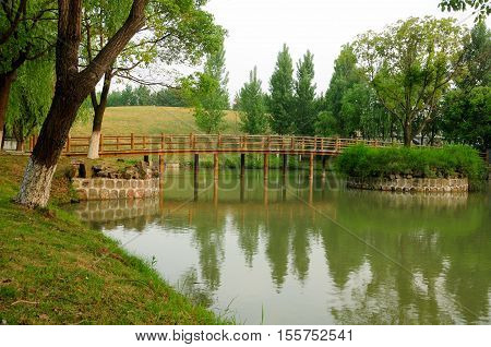 A wooden bridge crossing over a small manmade lake within the Three Kingdoms scenic area in wuxi china in Jiangsu province.