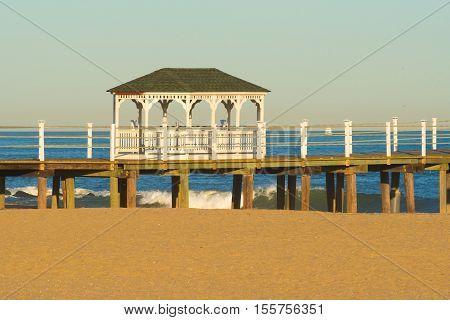 A gazebo built on a boardwalk jutting out over the ocean