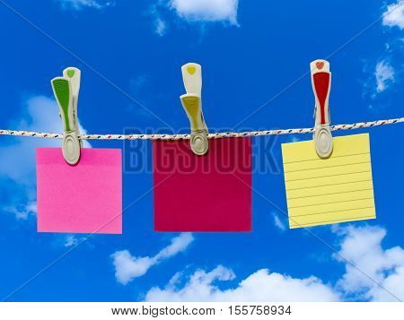 Three blank square of paper suspended from a washing line by plastic pegs against blue sky.