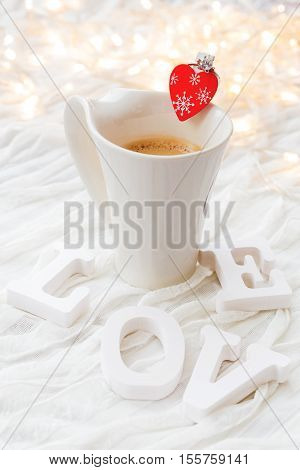 White cup of hot coffee with decorative heart and engagement diamond ring symbol of love and marriage. Valentine's day background with light bulbs and decorations.