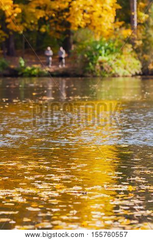 Two fishermens on the lake surrounded by golden autumn forest