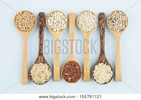 Various varieties of rice and wholegrains in spoon on wooden table background. Wheat barley millet oats rice coarse grain sorghum lotus seed.