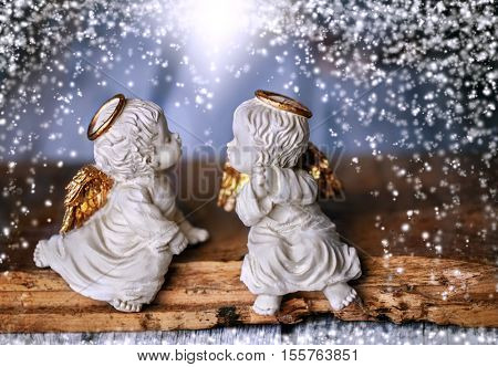 Two angel sitting on a piece of wood, falling snow around them