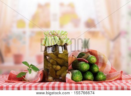 Fresh and glass jar with pickled cucumbers and spices on a background of the kitchen.