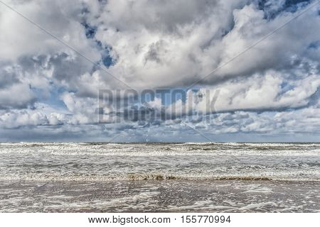 Waves advancing into the beach with lots of foam at the coast. Picture made at the island texel Netherlands