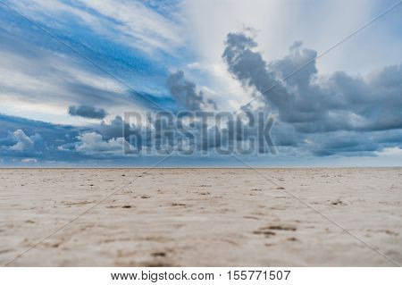 Beach in the Netherlands at sunset with solitary beach ands clouds