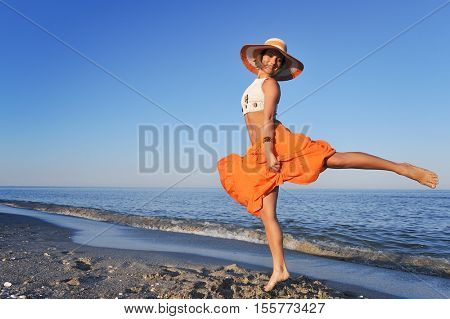 young happy woman dancing on the beach in summer