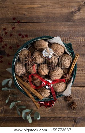 Walnuts with Christmas Decorations, Cinnamon, and Star Anise in Round Festive Tin on Rustic Wood Table