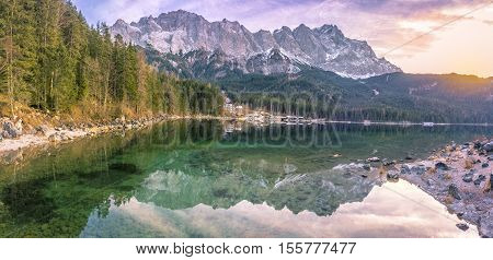 Alpine landscape with the German Alps mountains reflected in the Eibsee lake on a sunny day of December. Picture taken in Grainau Germany.