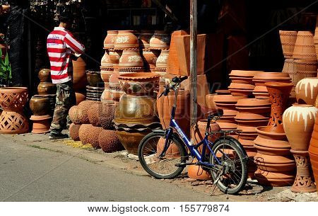 Chiang Mai Thailand - December 29. 2012: Customer and his parked bicycle at a Kamthieng Flower Market shop selling terra cotta planters saucers and vases