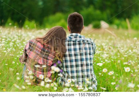 Loving couple having fun on summer vacation. Portrait of a happy couple laughing in field.Young couple in love outdoors. Summer holidays,  love.