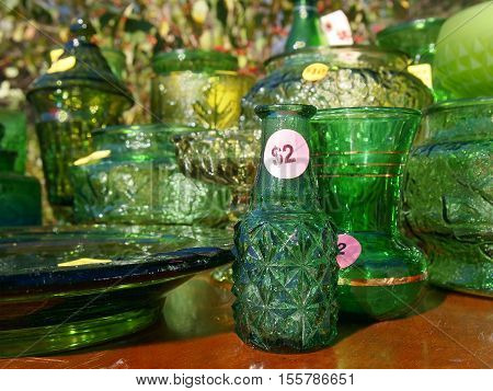 A collection of old vintage green glass vases dishes and other vessels for sale at a yard sale.