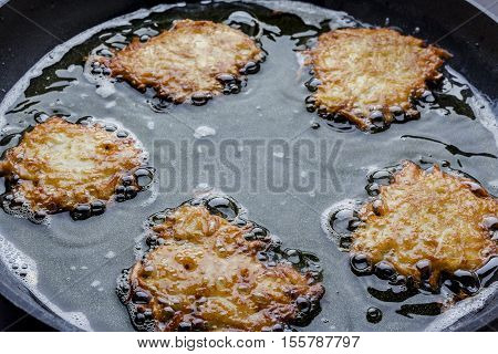 Frying latkes with ready side up in deep oil on the pan from side closeup