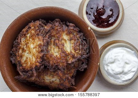 Latkes in a ceramic rustic brown bowl with sour cream and strawberry jam aside from above