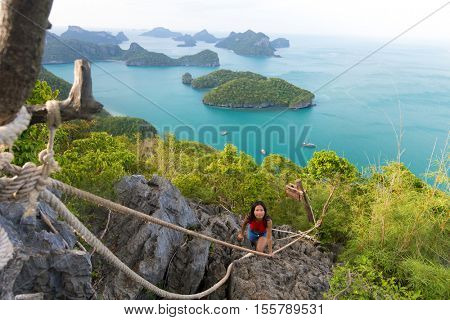 Woman climbing at the top of the Ko Angthong island viewpoint, Thailand