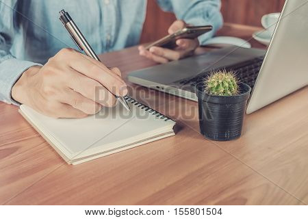 Young business man hands with pen writing notebook and using smartphone on desk table at office. Business concept.Vintage tone