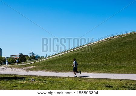 VIRGINIA BEACH, VIRGINIA - MAY 2, 2015:  People jog and walk on the trail surrounding Mount Trashmore Park enjoying the pleasant spring weather.