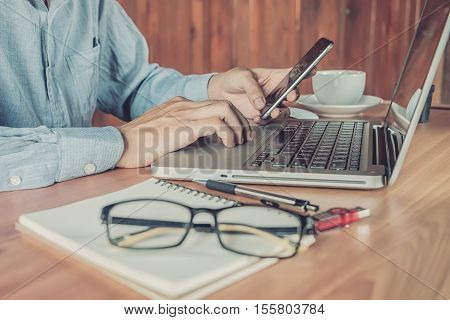 Business man hand holding smartphone and using laptop computer on desk table.Close up.Vintage tone.